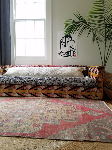 Liz Kamarul living room scene showing turkish rug layered over jute rug with vintage turkish rug turned into a pillow