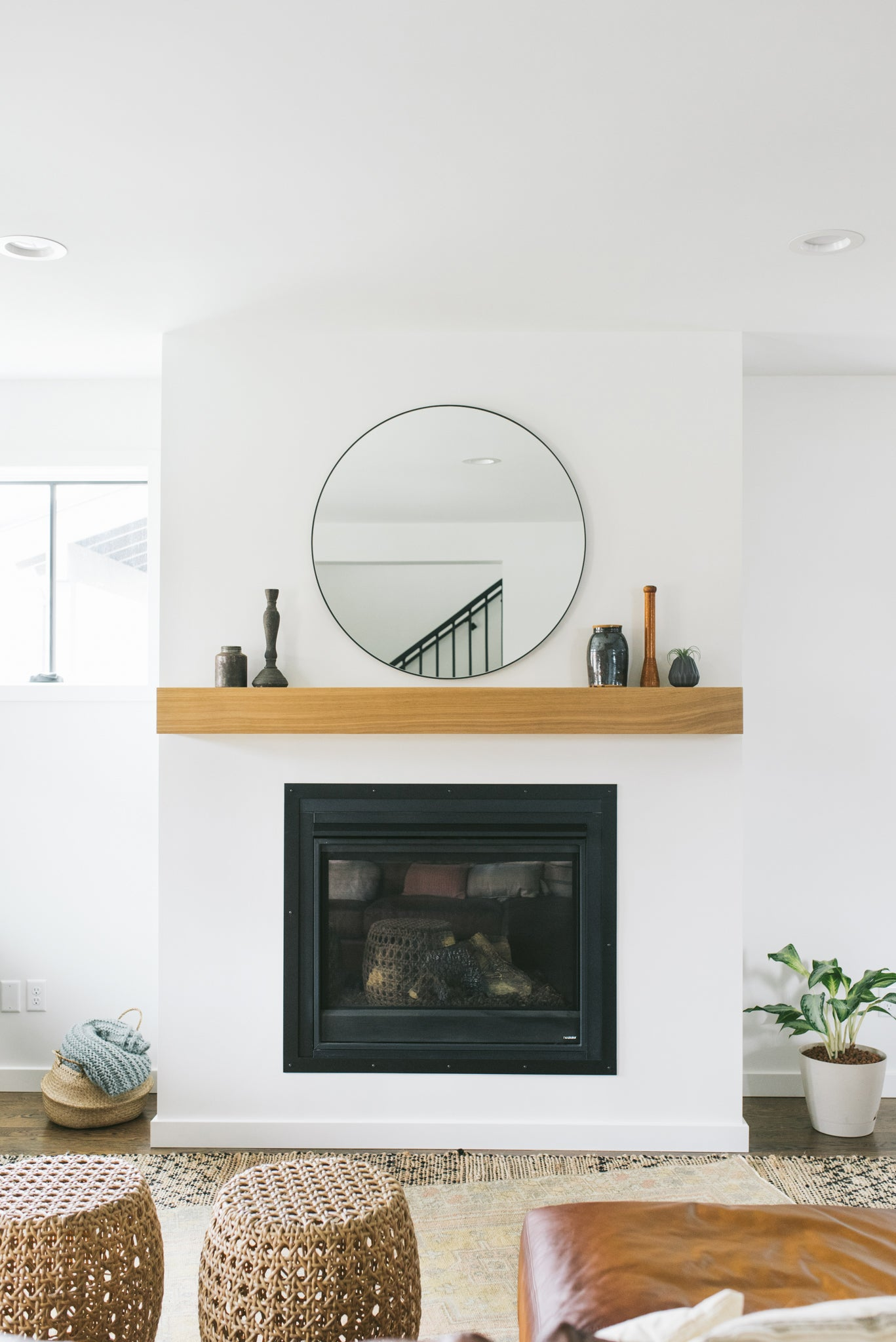 Minimalist contemporary fireplace in bright white with a birch mantel featuring small vintage finds.