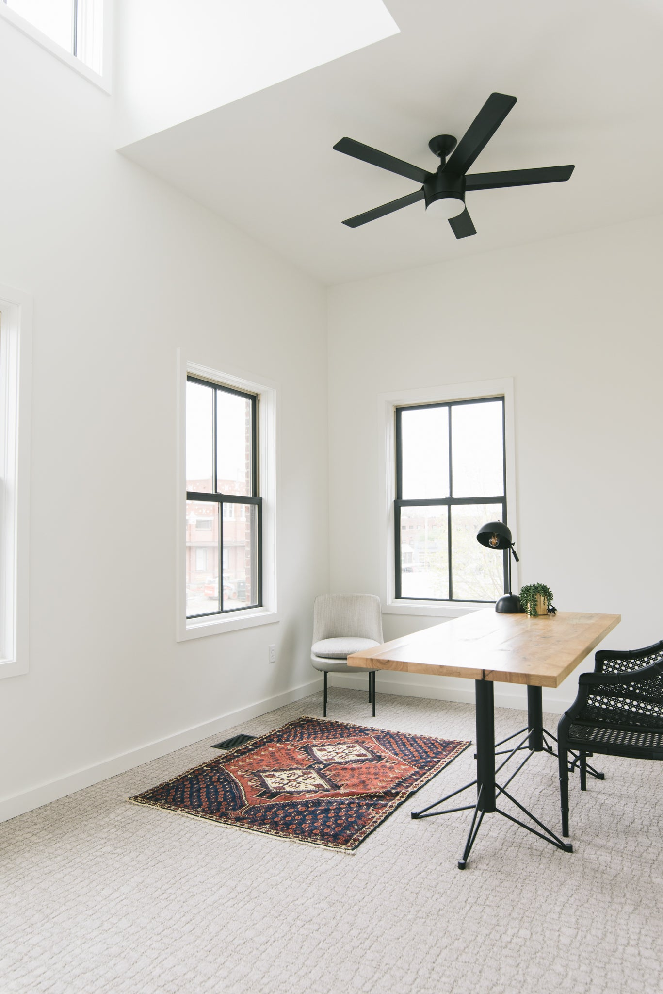 The newly built upstairs office featuring a wood drafting table desk, black caned chair, pale gray carpet, and white walls. A vintage diamond pattern rug with red and blue coloring ties the room together.