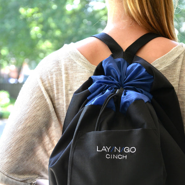 "Black and Blue Lay-n-Go CINCH (44"") backpack shown closed being carried by parent on back"