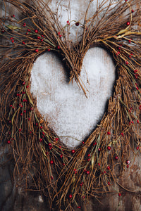 A wreath of twigs and natural materials in the shape of a heart