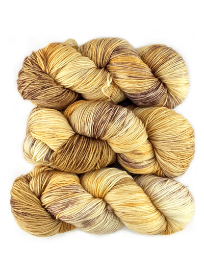 Three skeins of multicolored yellow and brown yarn