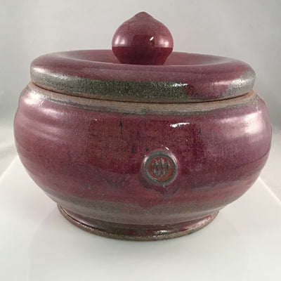 A red, lidded stoneware yarn bowl