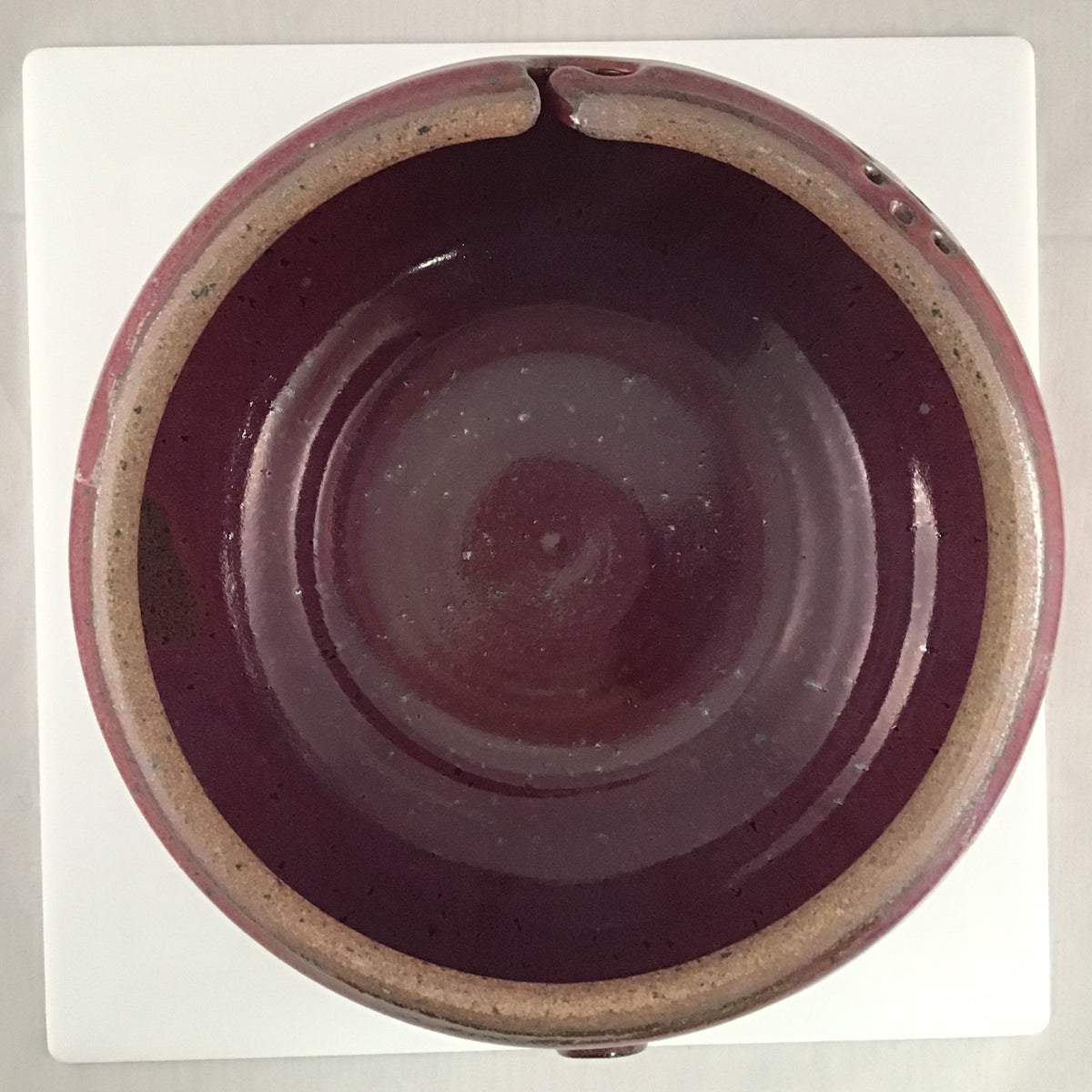 The inside of a red stoneware yarn bowl