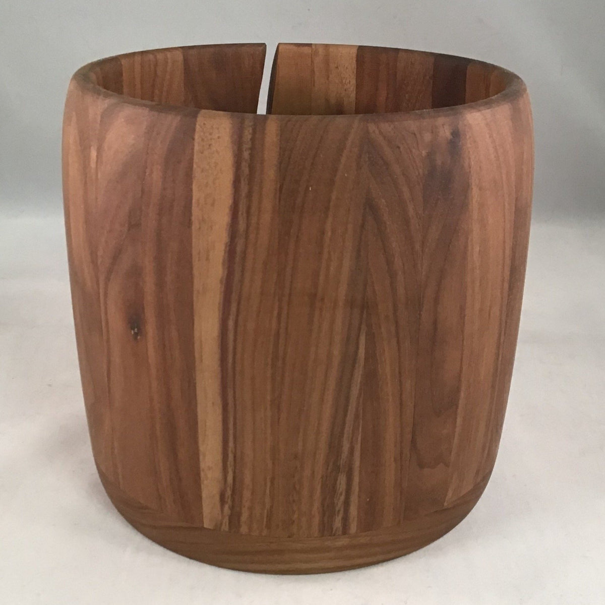 A wooden yarn bowl made from Walnut wood against a white backdrop