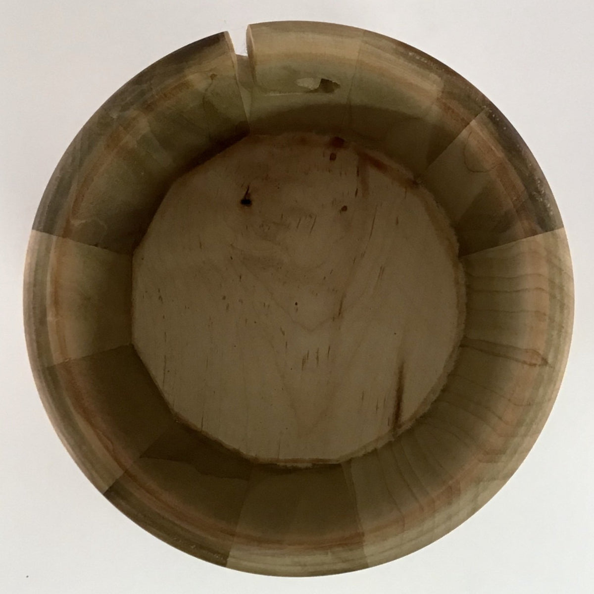 The inside of a wooden yarn bowl made from Poplar wood against a white backdrop