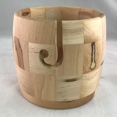 A wooden yarn bowl made from Ambrosia Maple wood against a white backdrop