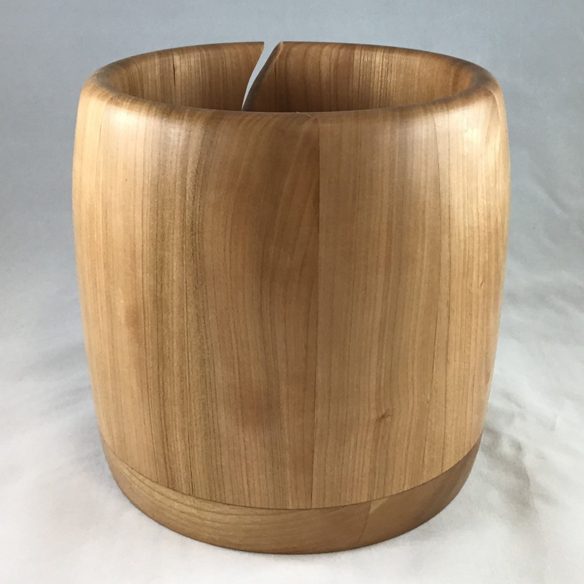 A wooden yarn bowl made from Cherry wood against a white backdrop