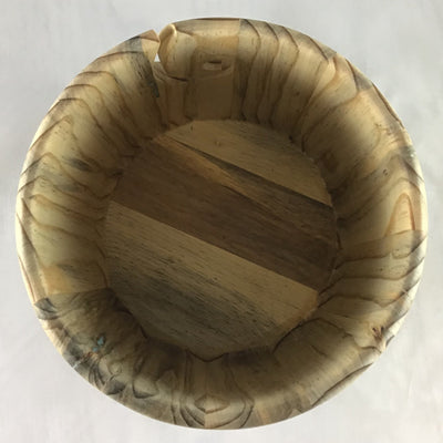 The inside of a wooden yarn bowl made from Ambrosia Pine Beetle kill wood against a white backdrop