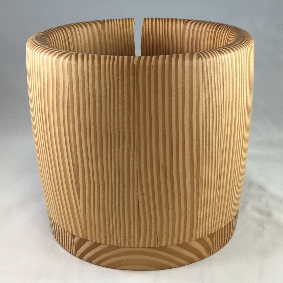 A wooden yarn bowl made from Douglas Fir wood against a white backdrop
