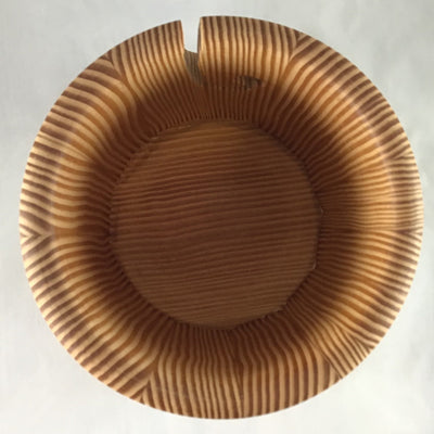 The inside of a wooden yarn bowl made from Douglas Fir wood against a white backdrop
