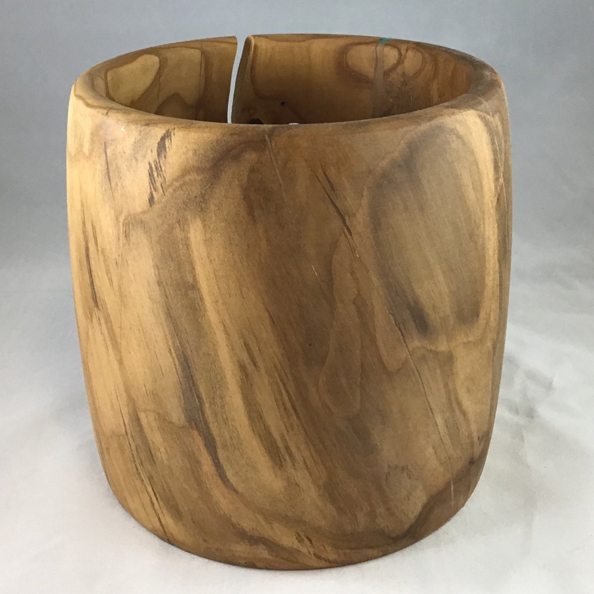 A wooden yarn bowl made from Apricot wood against a white backdrop