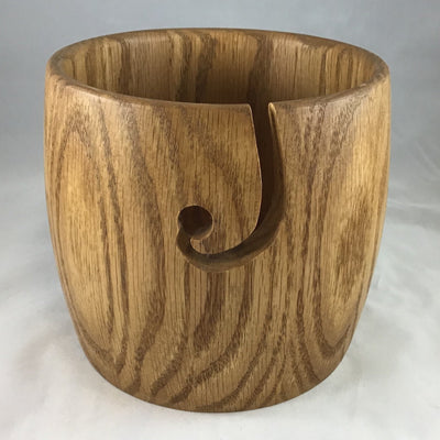 A wooden yarn bowl made from Oak wood against a white backdrop
