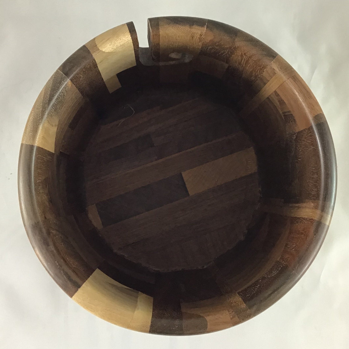 The inside of a wooden yarn bowl made from Walnut wood against a white backdrop