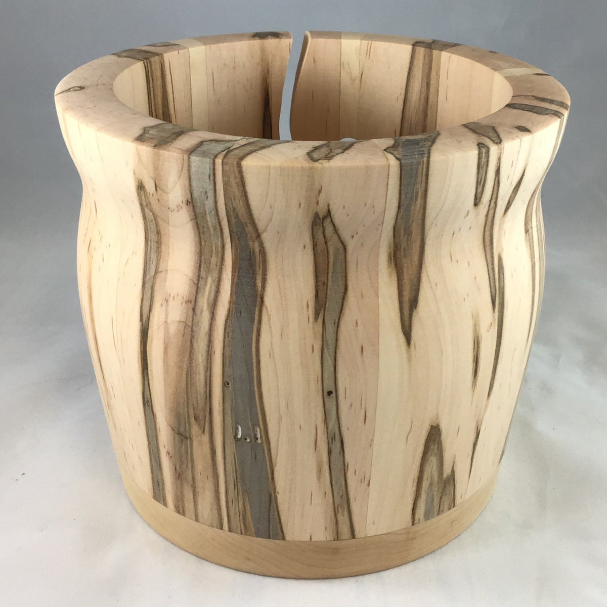 A wooden yarn bowl made from Ambrosia Ambrosia Maple wood against a white backdrop