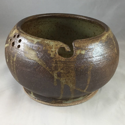 A dark brown stoneware yarn bowl