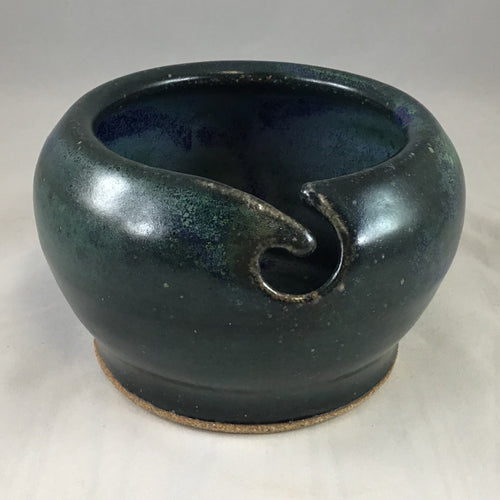 A dark green stoneware yarn bowl