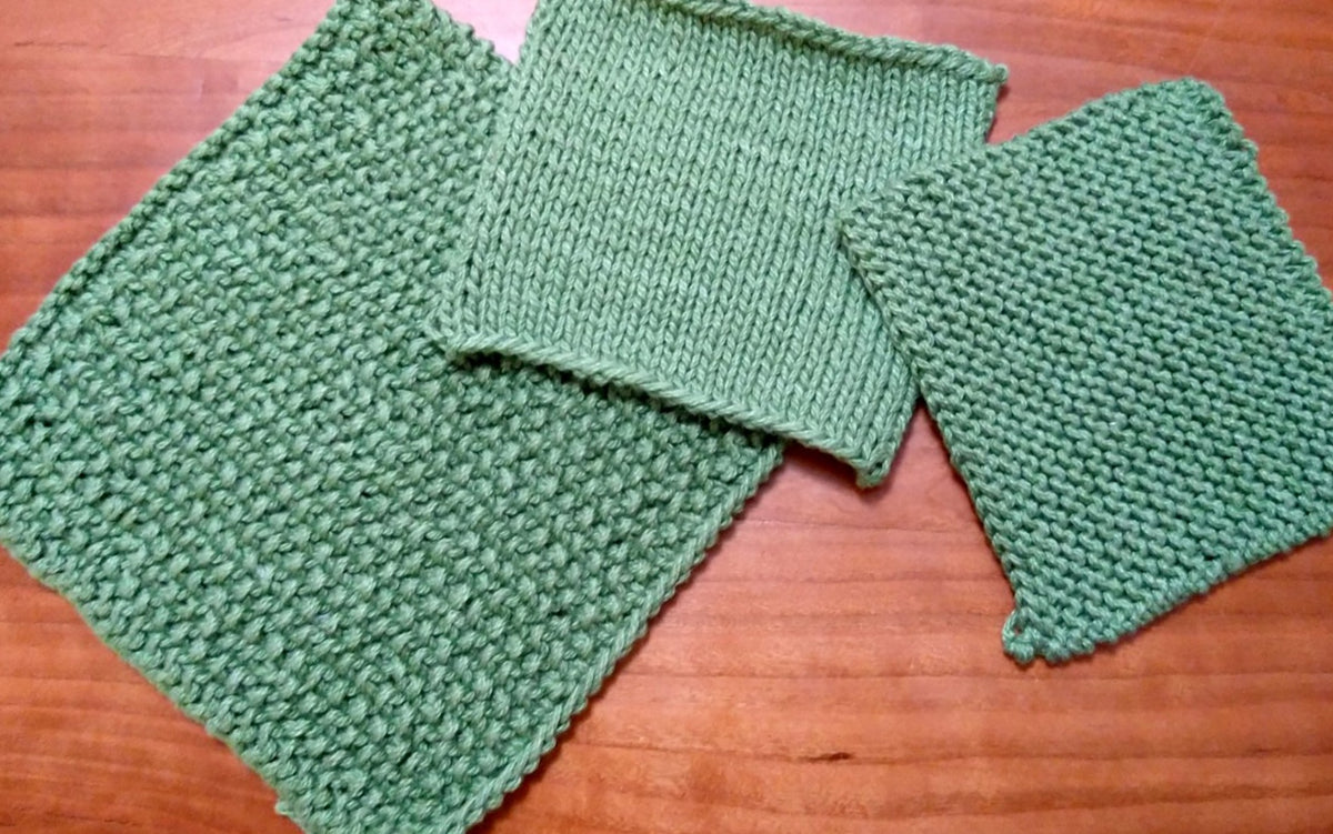 Three green knitted squares on a wooden surface