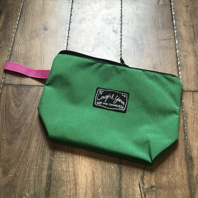 A bright green, zippered pouch featuring the Cowgirl Yarn logo