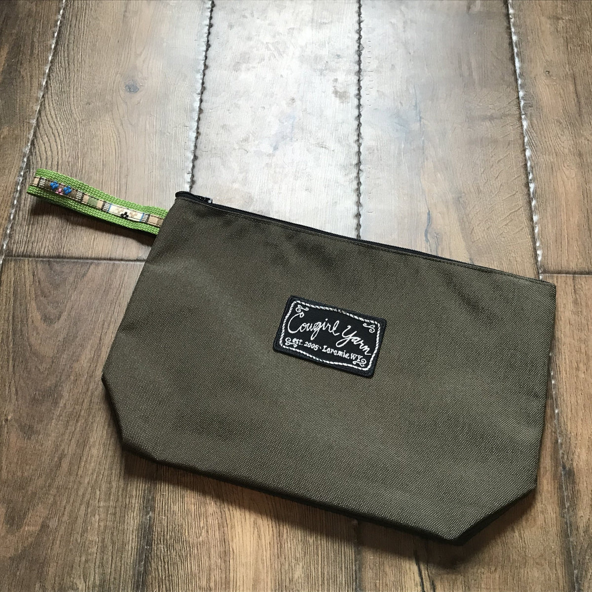 An olive green, zippered pouch featuring the Cowgirl Yarn logo