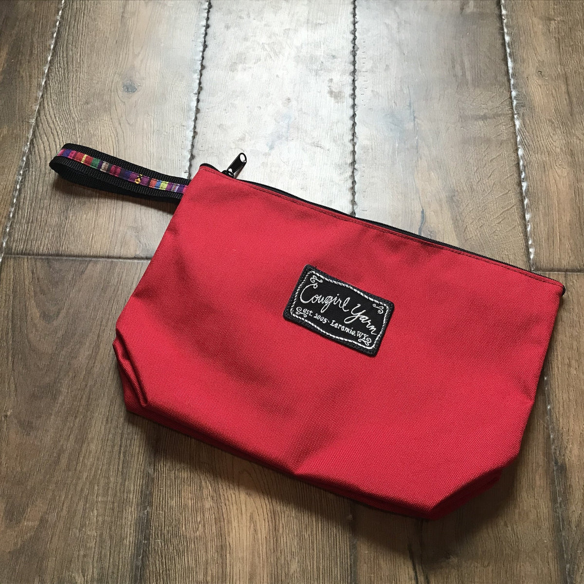 A bright red, zippered pouch featuring the Cowgirl Yarn logo