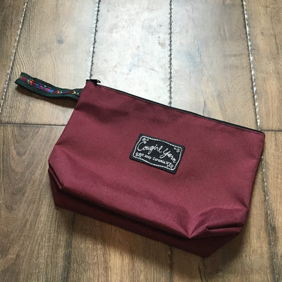 A maroon, zippered pouch featuring the Cowgirl Yarn logo