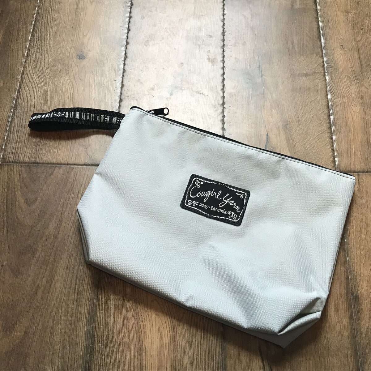 A white, zippered pouch featuring the Cowgirl Yarn logo