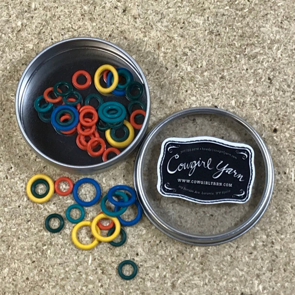 A Cowgirl Yarn branded metal tin filled with rubber stitch markers in multiple colors
