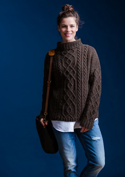 A woman wearing a knitted, cabled sweater