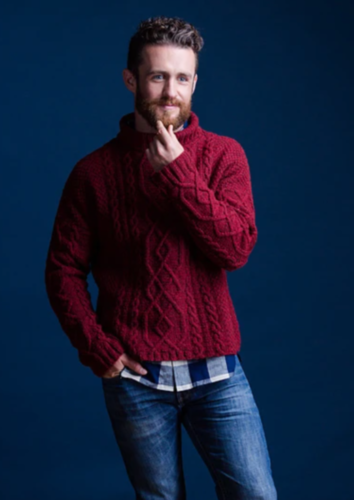 A man wearing a knitted, cabled sweater