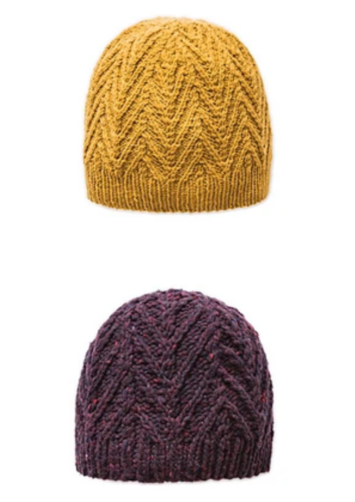 Two knitted, cabled hats on a white background