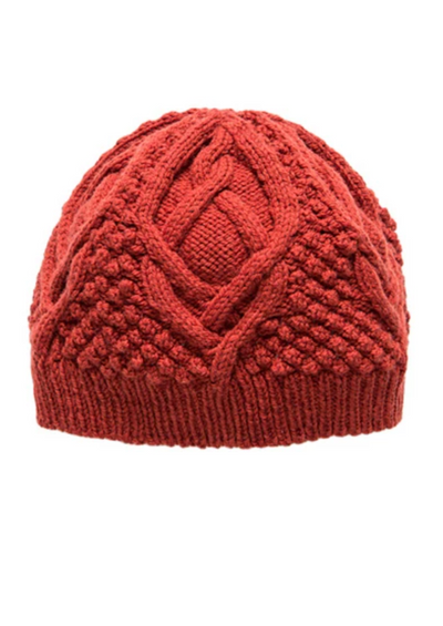 A knitted cable hat on a white background