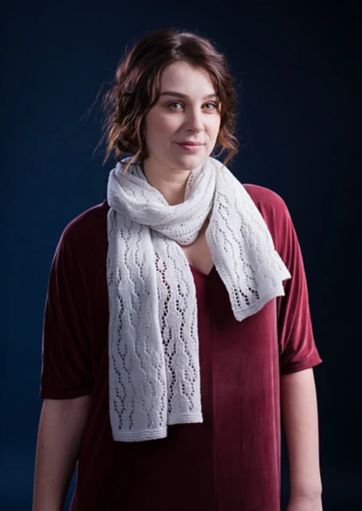 A woman wearing a white, knitted shawl