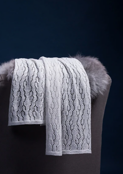 A white, knitted shawl thrown over a chair back