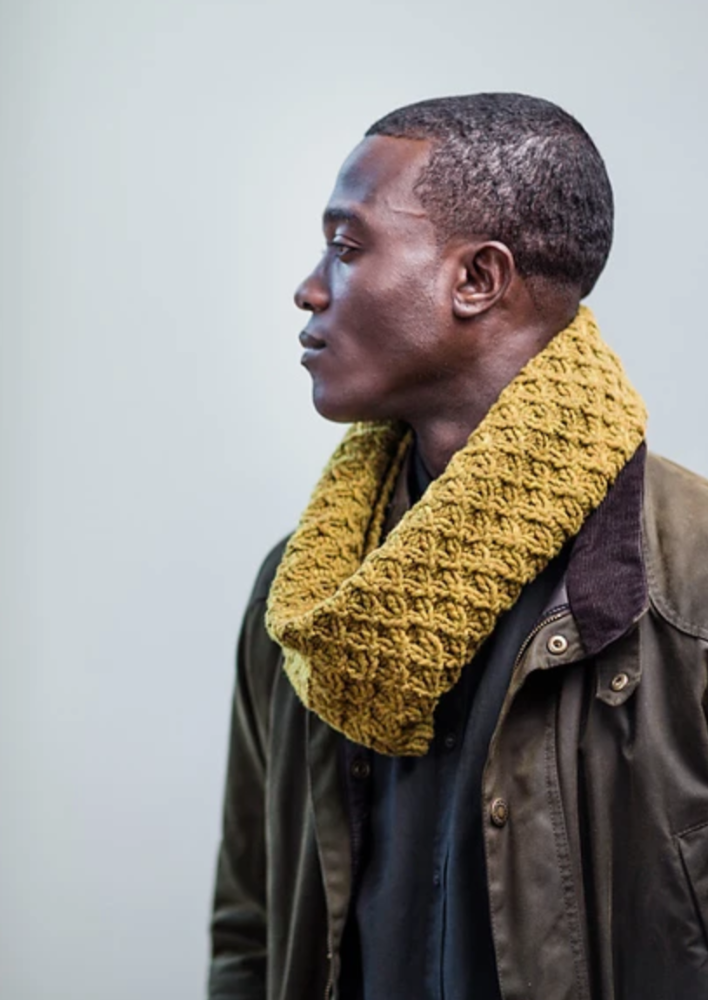 A man wearing a cabled, knitted cowl