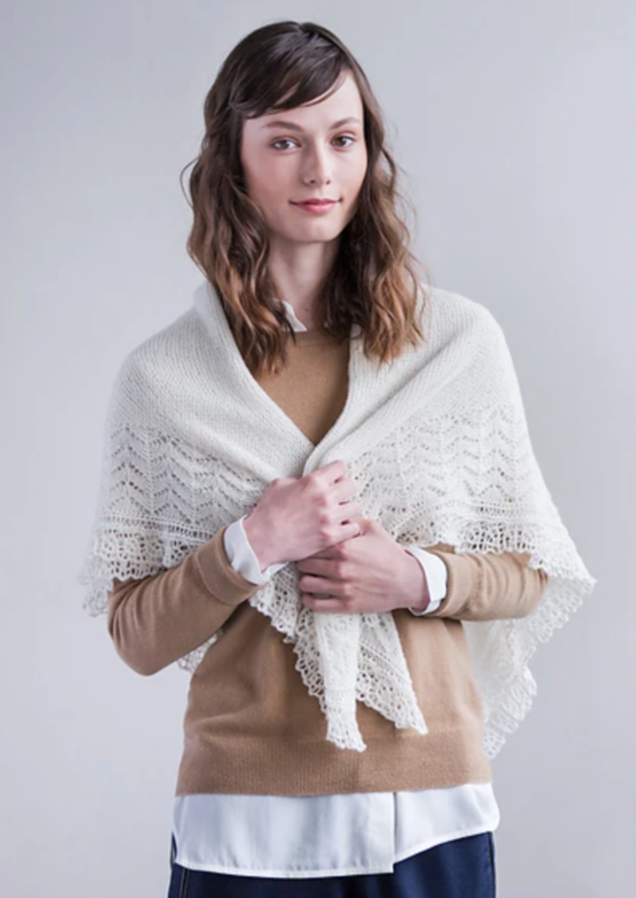 A woman wearing a cream lace shawl