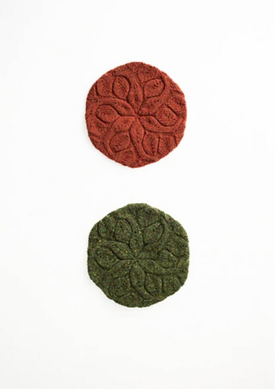 Two knitted berets on a white surface
