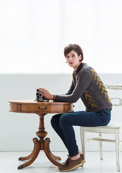 A sitting woman wearing a knitted sweater