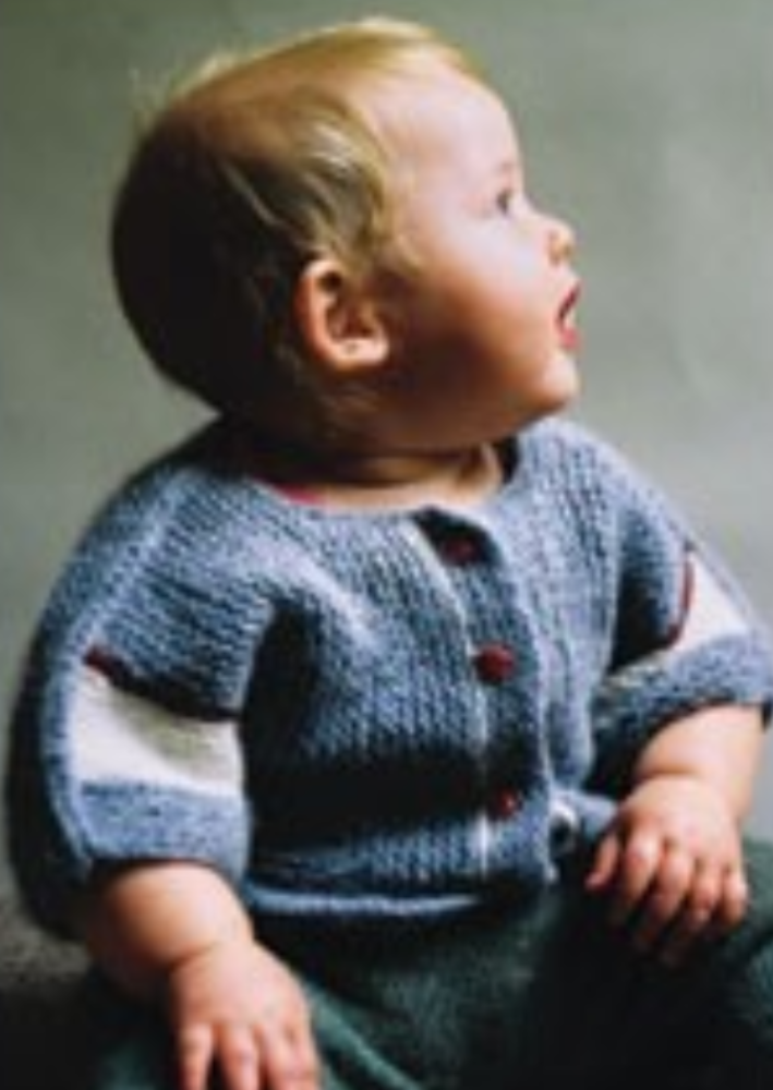 A baby wearing a knitted jacket