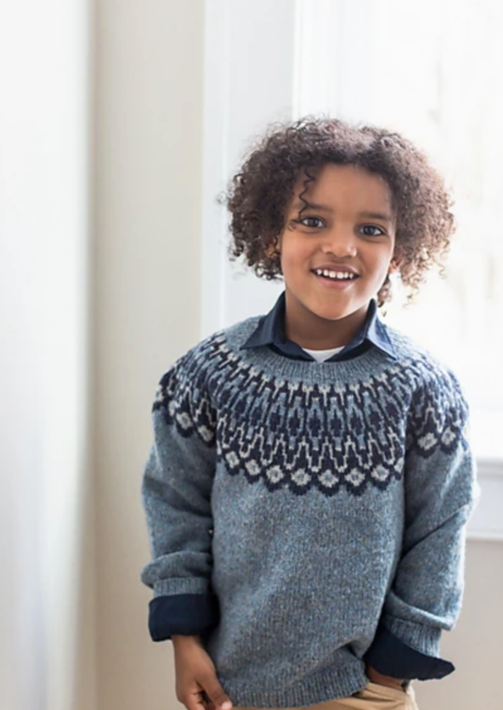 A boy wearing a knitted sweater