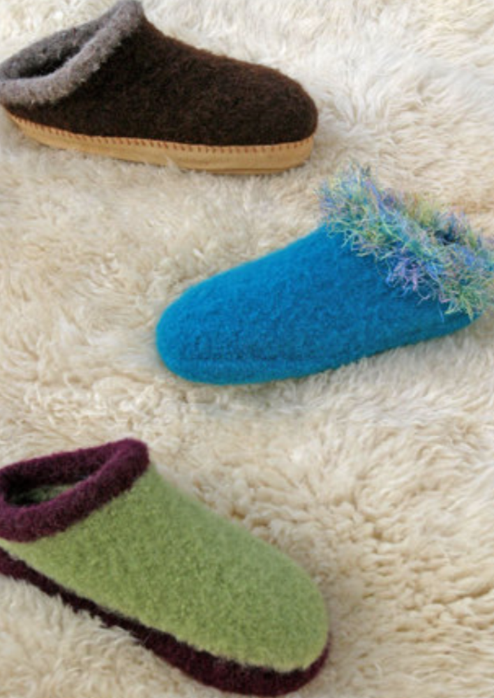 Three felted clogs on a furry surface