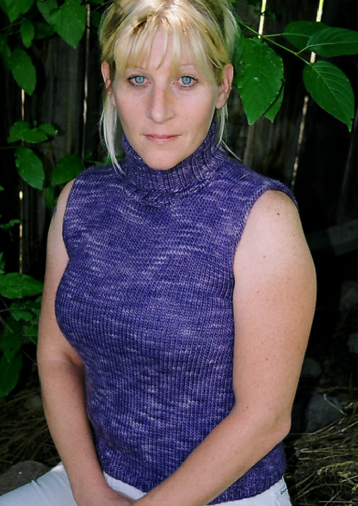 A woman wearing a sleeveless, knitted, turtleneck sweater