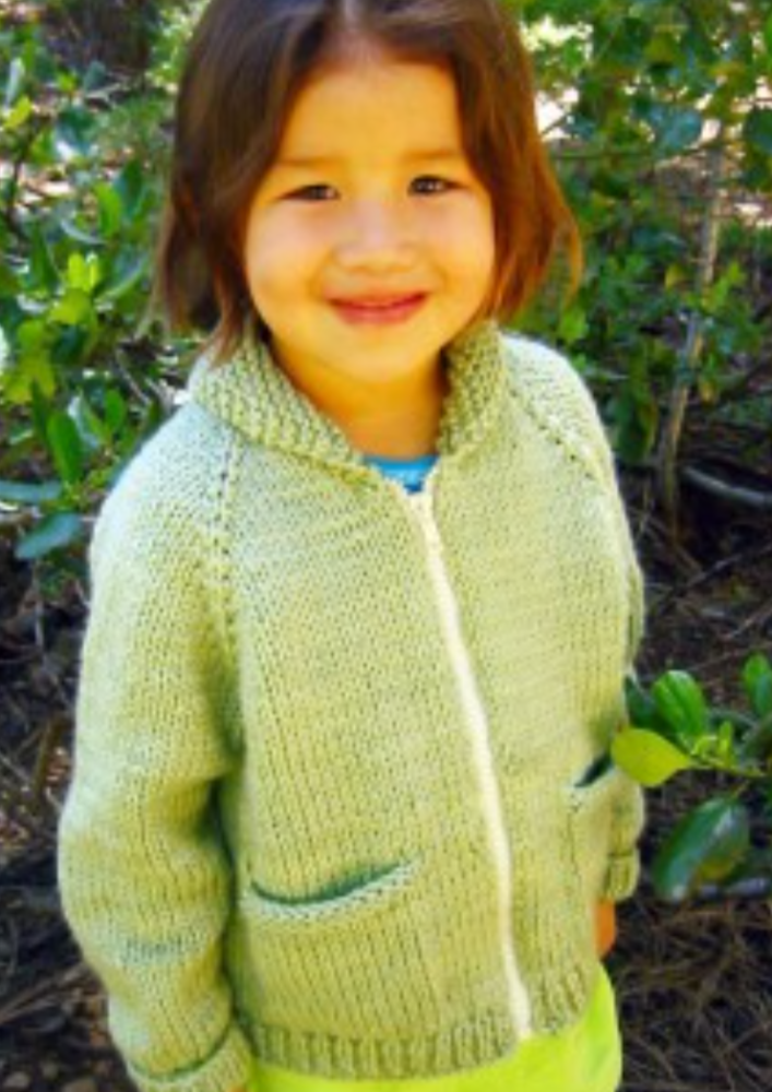 A child wearing a knitted jacket