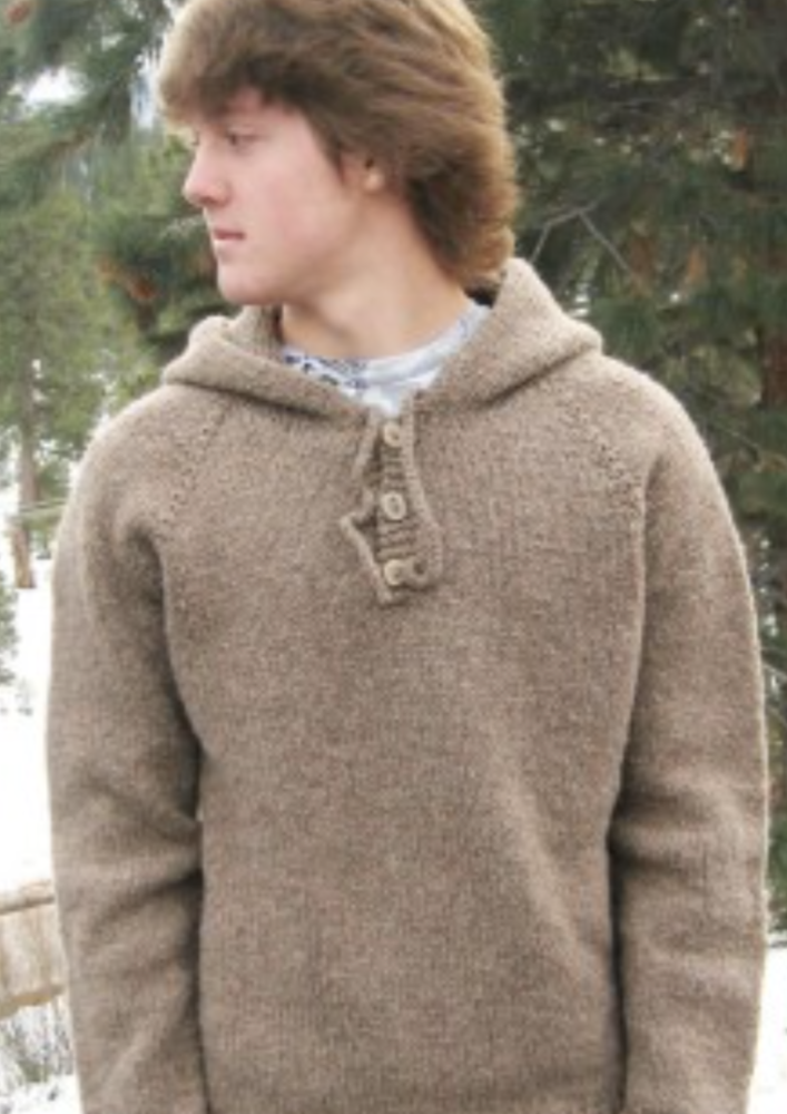 A man wearing a knitted sweater with hood