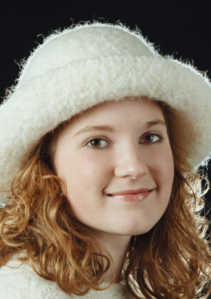 A girl wearing a white, felted hat with brim