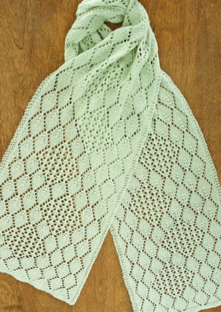 A lacy, knitted scarf on a wooden surface