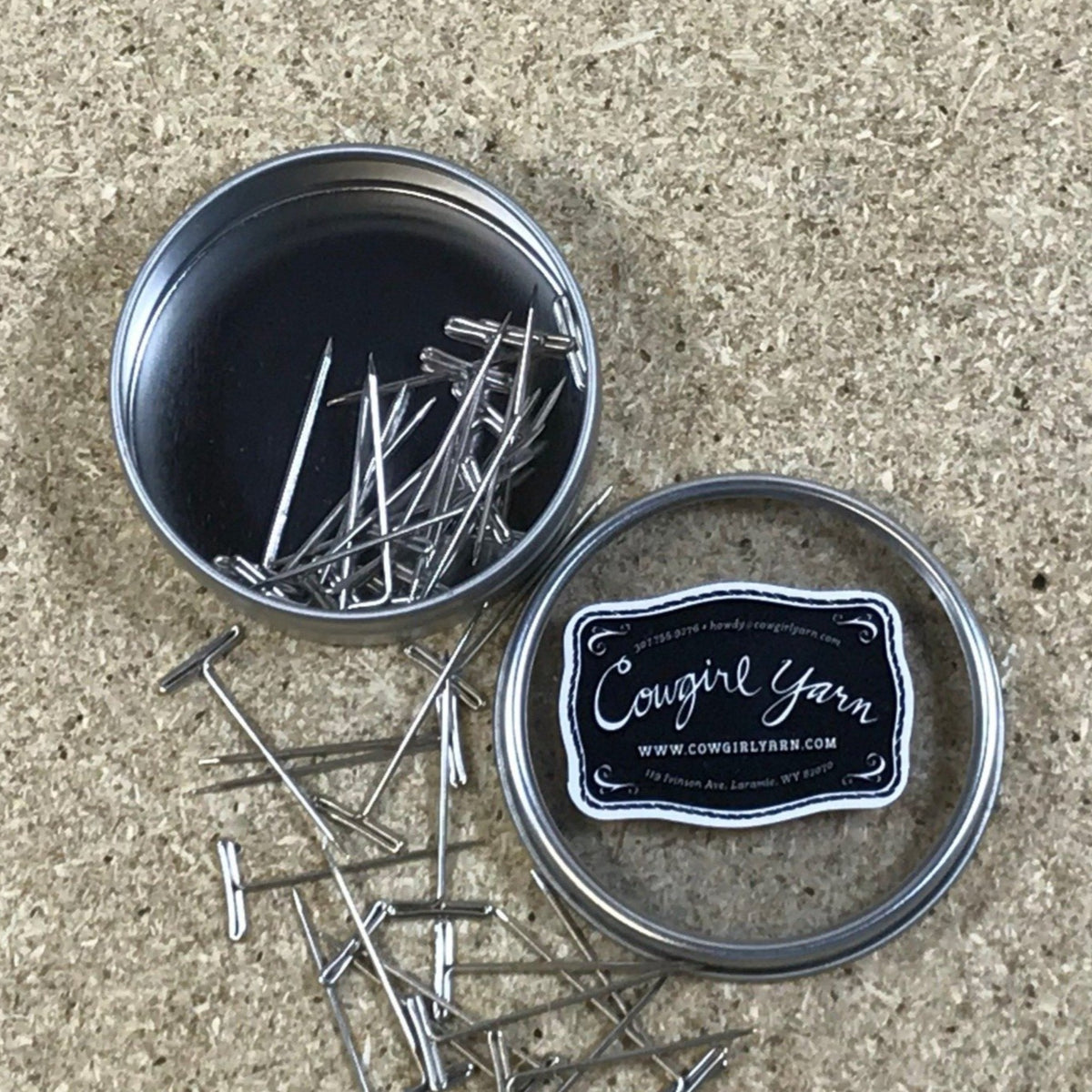A Cowgirl Yarn branded metal tin filled with stainless steel T pins