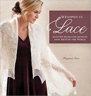 "The book cover for ""Wrapped in Lace"" featuring a woman wearing a white knitted shawl, which says, ""Knitted heirloom designs from around the world."""