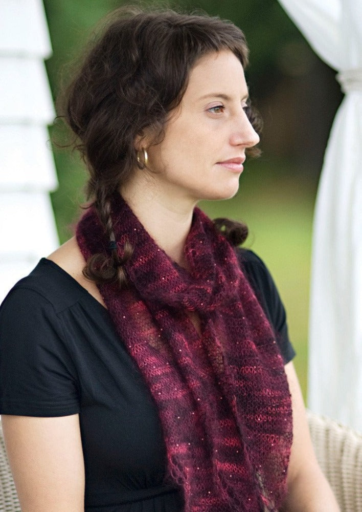 A woman wearing a beaded, knitted scarf
