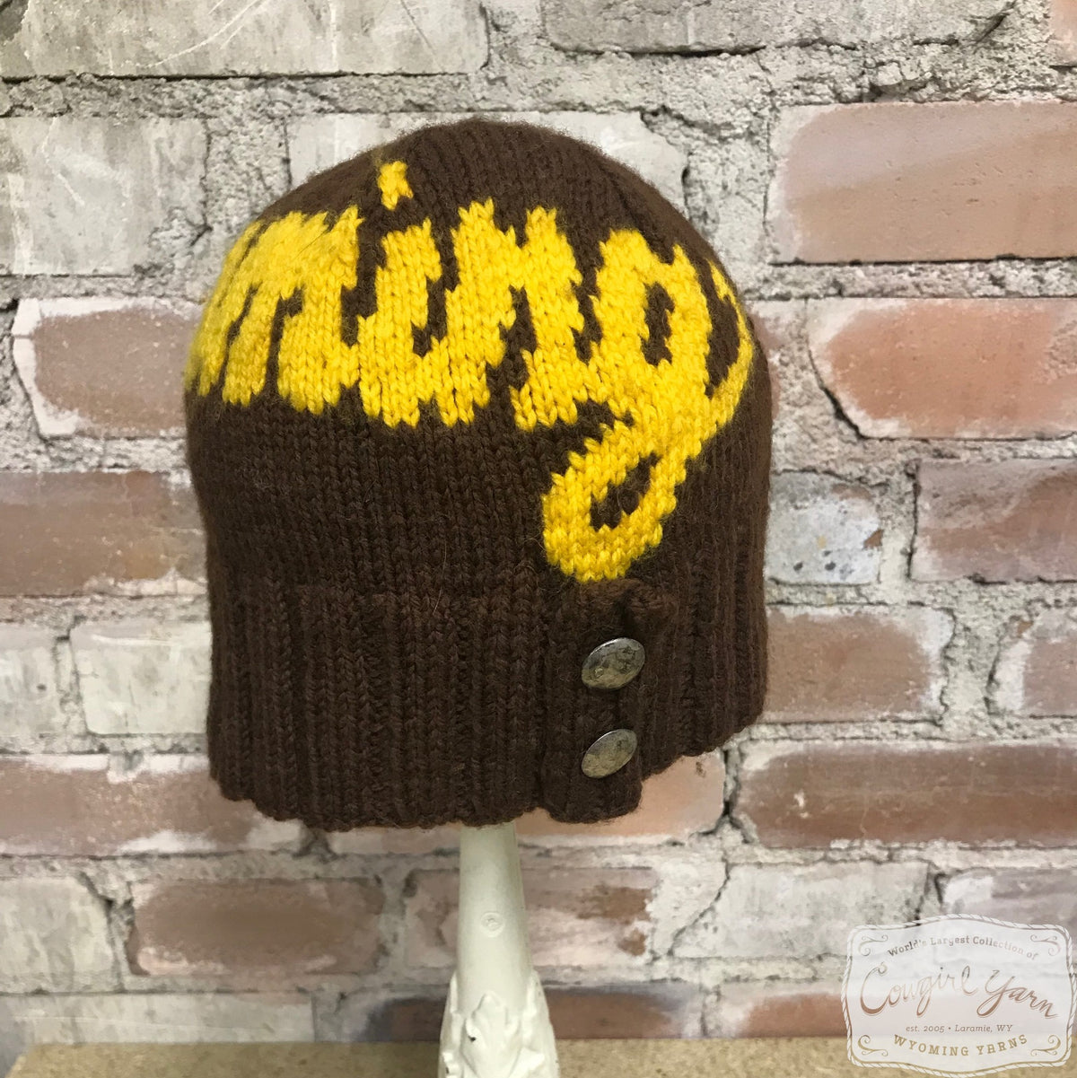A brown and gold beanie hat with buttons that says Wyoming